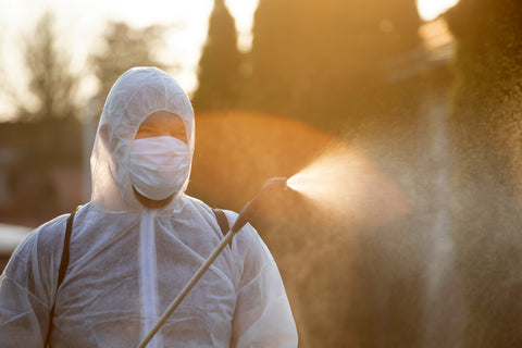 A person in PPE kit sanitizing the surroundings