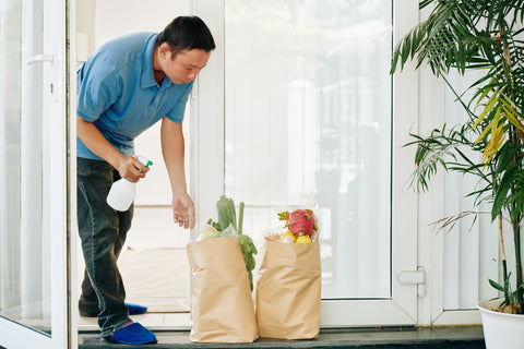 A person sanitizing the grocery bags