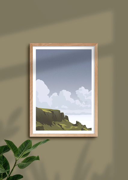 Framed art print of the green and lush Quiraing landscape on the Isle of Skye, Scotland, with sunshine peeking through stormy clouds.   Inspired by vintage British rail travel posters, the style is limited to a few colours with paired back detailing to keep it calm and minimal.