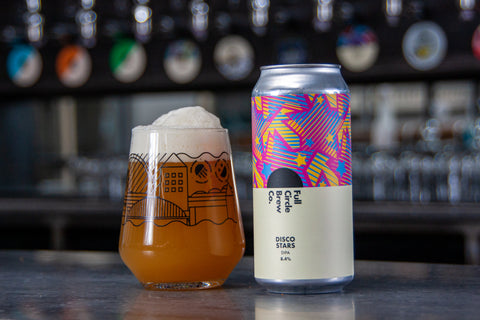 Can of the latest brew from Full Circle, a Double India Pale Ale, 8.4%, consisting of Grapefruit, Citrus and Tropical Fruit Flavours. With a glass full of the alcoholic beverage sat on top of a bar.