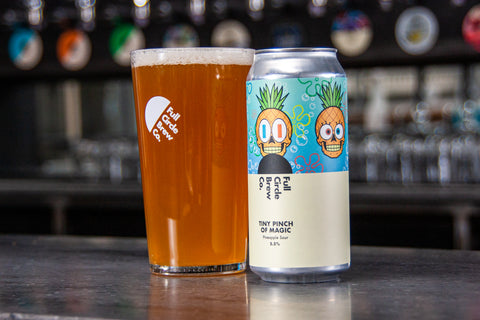 A Can and full pint of Tiny Pinch of Magic, a Pineapple Sour brewed by the team at Full Circle Brew Co. Sat on top of a bar in their Hoults Yard Taproom.