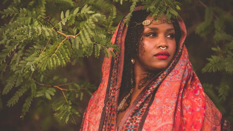 Gorgeous Brown SKin woman with red lipstick and natural coiled hair falling on her shouler. Draped in a red and violet blue shawl like royalty.