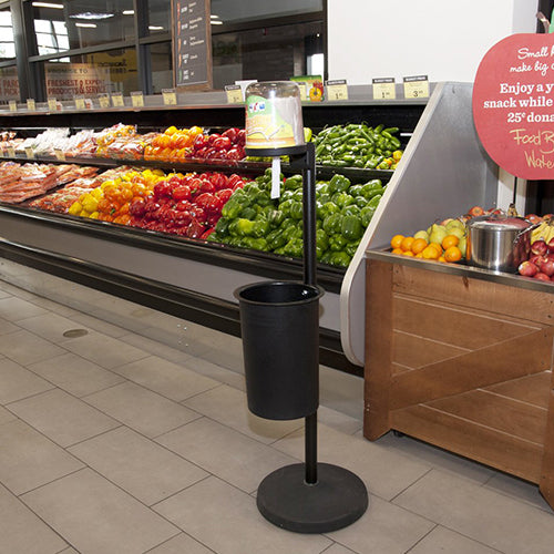 CitrusWirx disinfectant wipe dispenser on black stand in grocery store produce section
