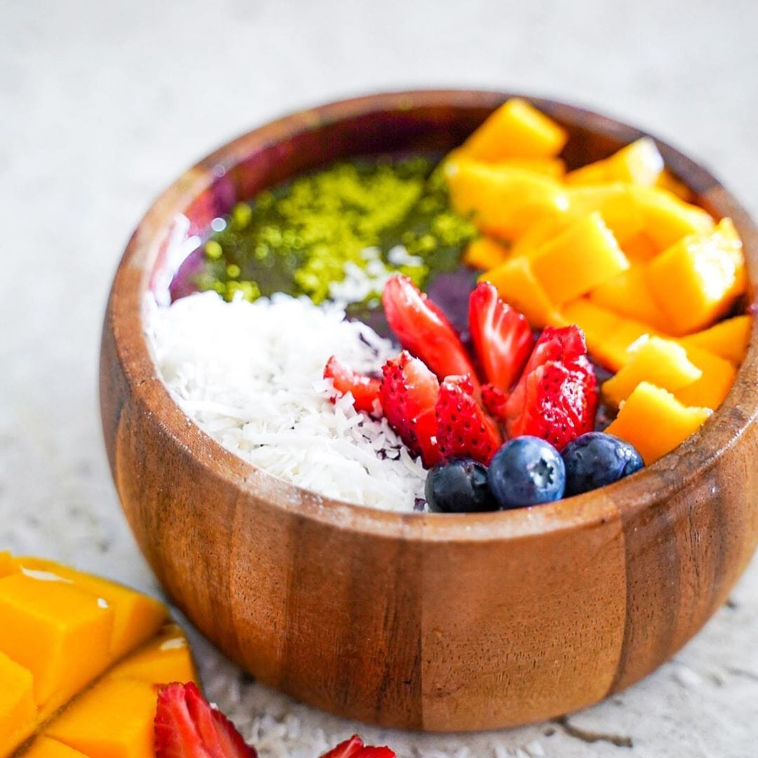tropical smoothie bowl with fresh fruit in acacia wood bowl