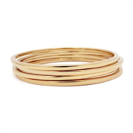 stacked set of four thin gold classic bangles