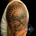 Religious Tattoo Of Jesus On The Upper Arm In Black And Gray With Roman Numerals Tatuaje Religioso De Jesus En El Brazo Con Numero Romanos Y Tinta Negra Y Gris
