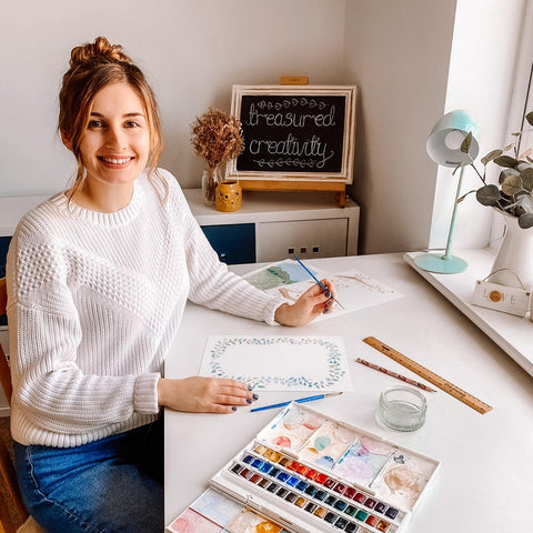 Picture of Beth the business owner of Treasured Creativity. A photo of Beth from Treasured Creativity sat in her art studio surrounded by her watercolour paintings.
