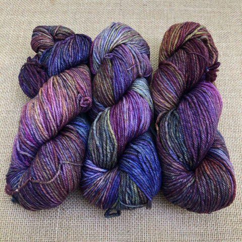 Malabrigo Rios Quegay has variegated shades of purple, brown, green, blue, pink, and gold