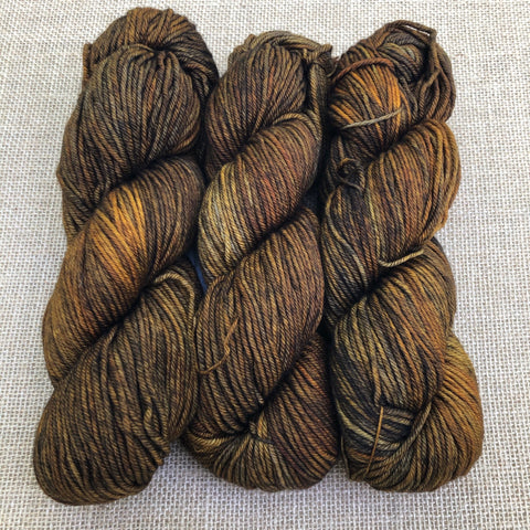 Malabrigo Rios Glitter is variegated shades of ochre gold, rust and some warm brown