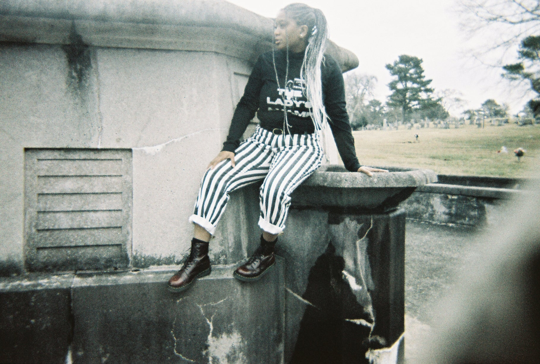 Faded image shot on film of black alternative model with long grey braids wearing the The Lady's a Vamp tee and black and white striped pants in a graveyard.