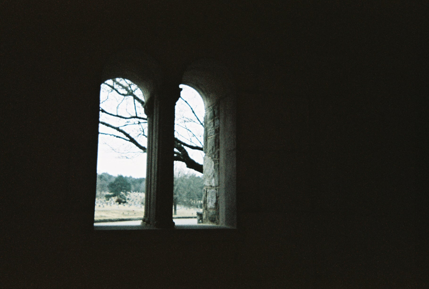 Faded film photo of dark archway looking out at a cemetery on a cloudy day.