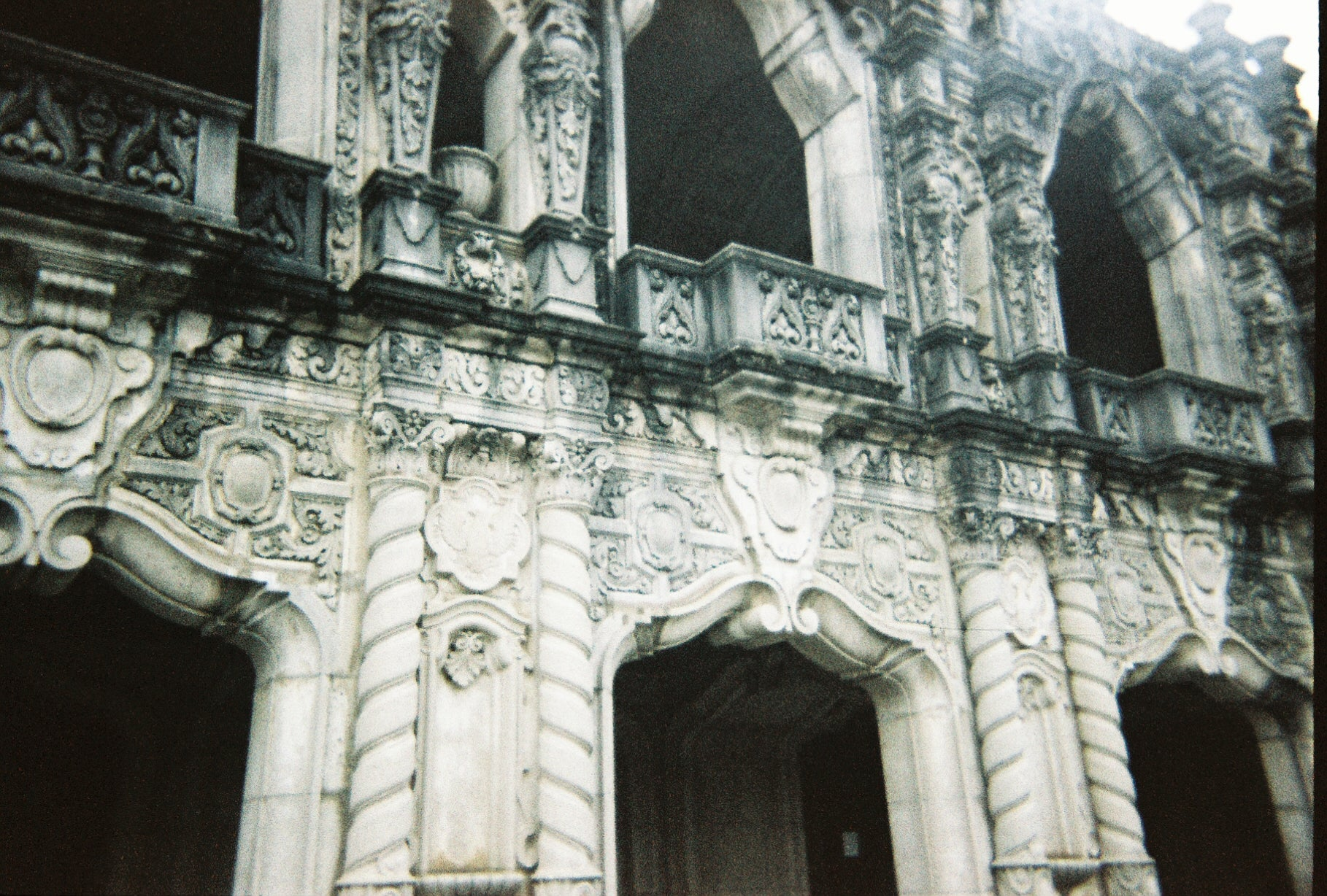 Faded film photo of large intricate grey archways in Atlanta's Westview Cemetery on a cloudy day.