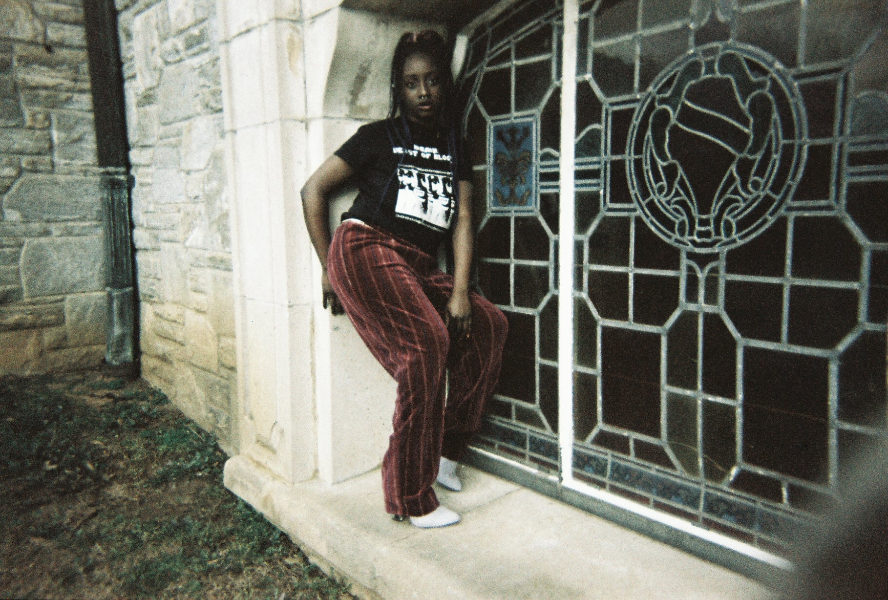 Faded film photo of black female goth model with long blue braids and septum piercing wearing the Darkness Mixed With Light Fitted Tee and striped red velvet pants, posing in front of large stained glass in a cemetery.