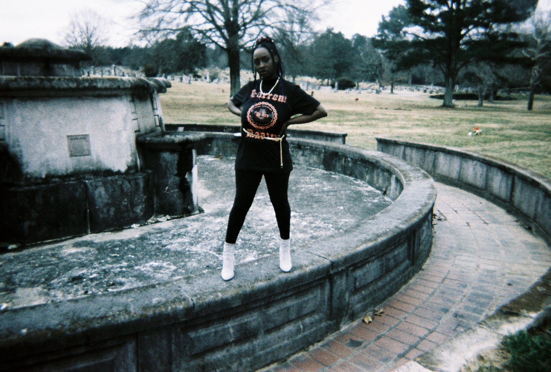 Faded film shot of black female goth model with long blue braids posing in the middle of a frozen fountain, wearing the Sorrow Is Her Master Tee, striped red velvet pants, white boots, and gold accessories.