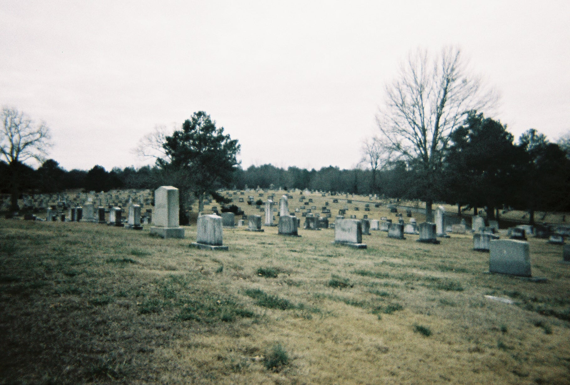 Wide faded film photo of many graves on a cloudy day in Atlanta's Westview Cemetery.