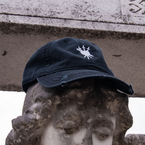 The Stake Through My Love Distressed Hat posed on top of the head of a stone angel sculpture in Atlanta's Westview Cemetery.