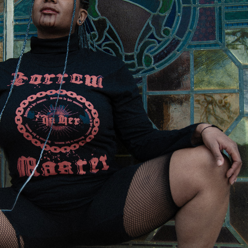 Black goth female model with long grey ombre braids wearing the Sorrow Is Her Master Tee, paired with a black turtleneck and fishnet biker shorts, posing in front of stained glass in Atlanta's Westview Cemetery.