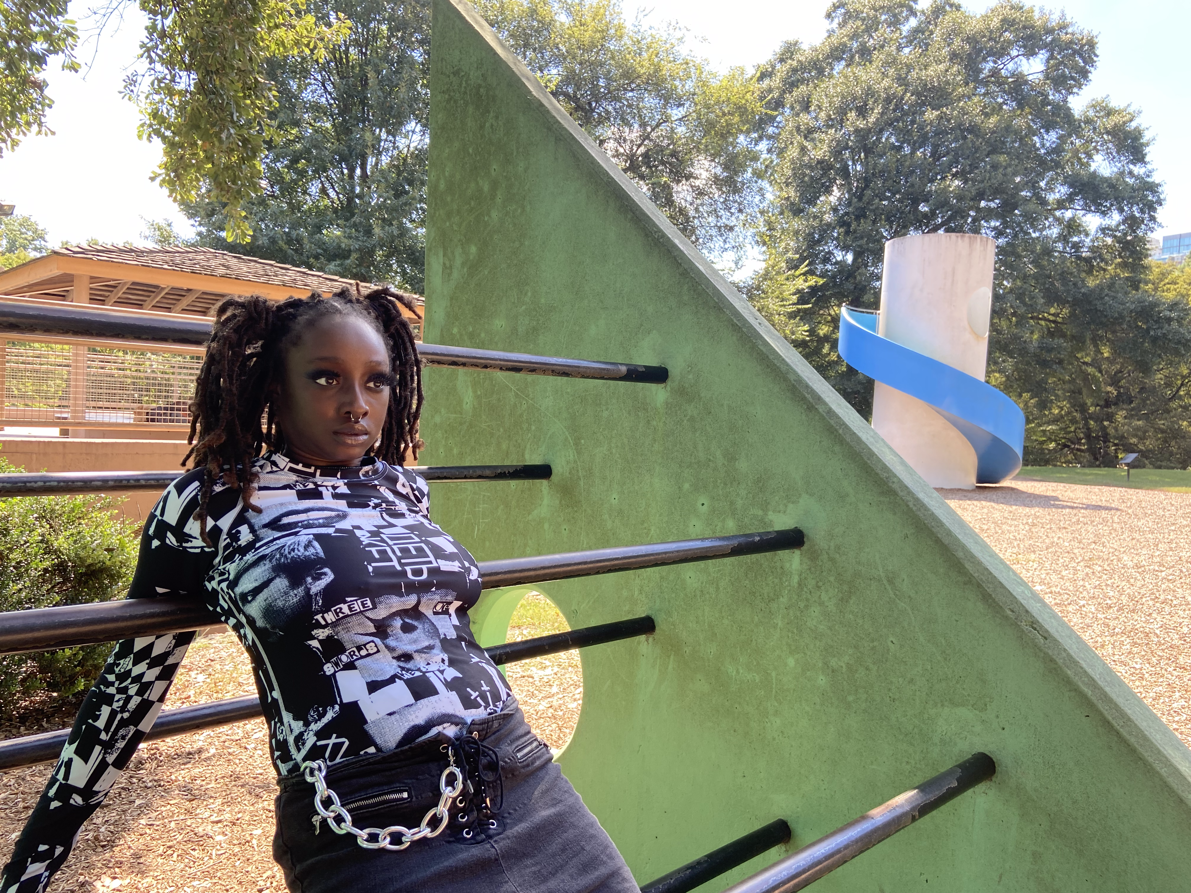 Black alternative model with dreadlocks posing in a dystopian-type playground while wearing the Soviet Discotheque Long Sleeve and ripped black jeans.