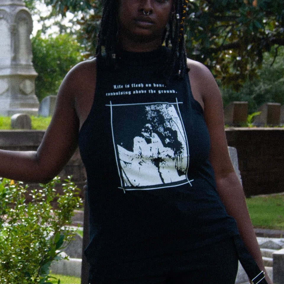 Black woman with braid bob wearing black sleeveless mock neck with a gothic graphic from the film Begotten in a graveyard. Item from Three of Swords' Collection 2: Betwixt Two Veils.