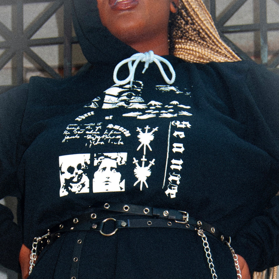 Black woman with long blonde braids in a black hoodie with a white collage-inspired gothic graphic on the chest, styled with a small black belt. Item is from Three of Swords' Collection 2: Betwixt Two Veils.