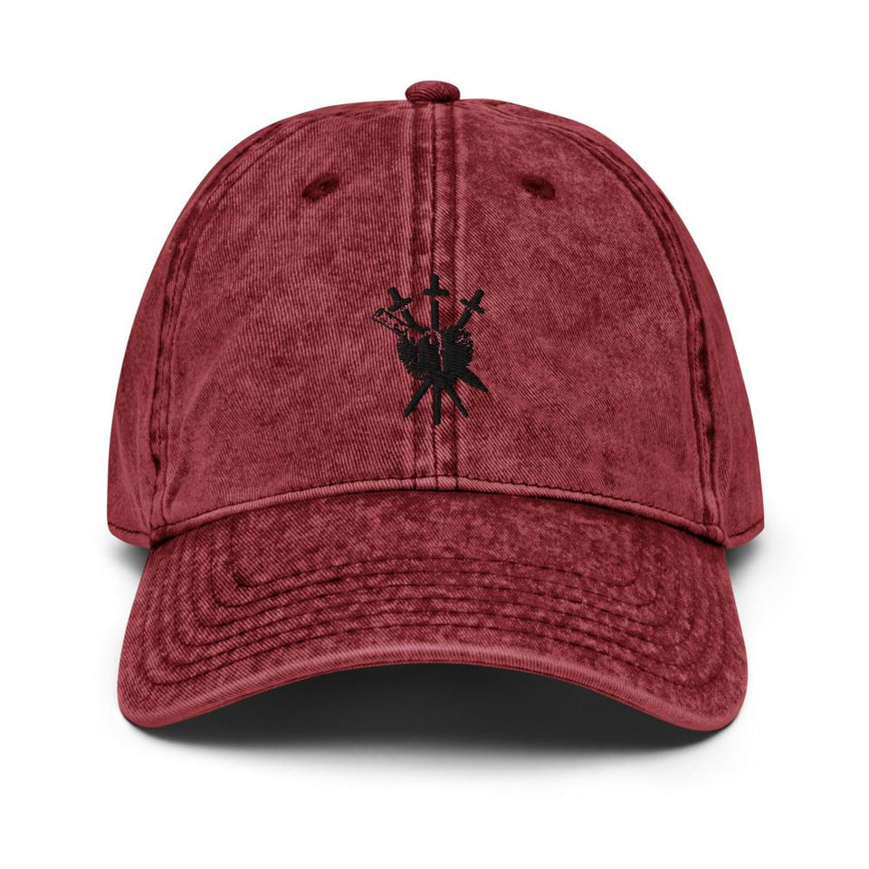 Dark red vintage hat with black embroidered Three of Swords logo with stake going through the center, placed in the front center of the cap