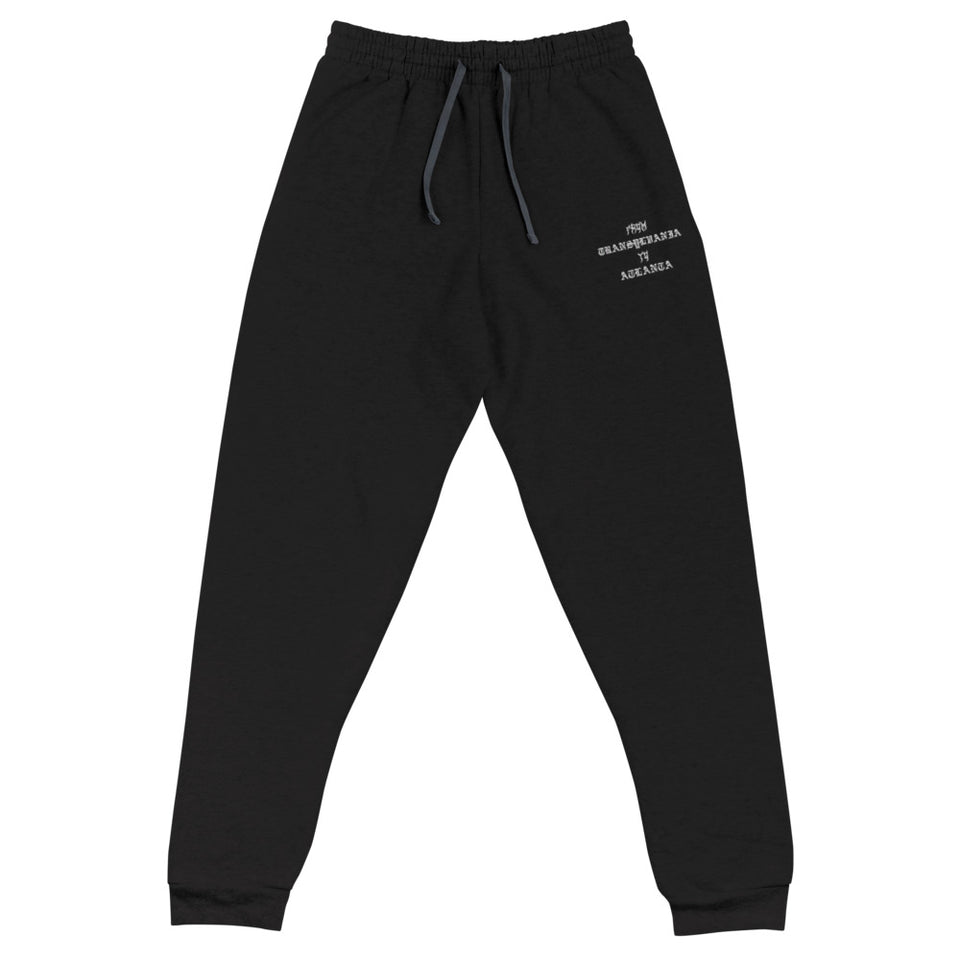 "A mockup of a pair of black cotton and polyester fleece joggers with one embroidered graphic on the left upper thigh area that says ""From Transylvania to Atlanta"" in white embroidered metal and medieval goth text."