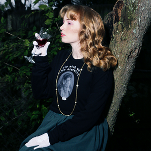 Image of white female model wearing the Eternity Crop Sweatshirt while sitting in front of a tree and holding a glass of red wine to her lips.