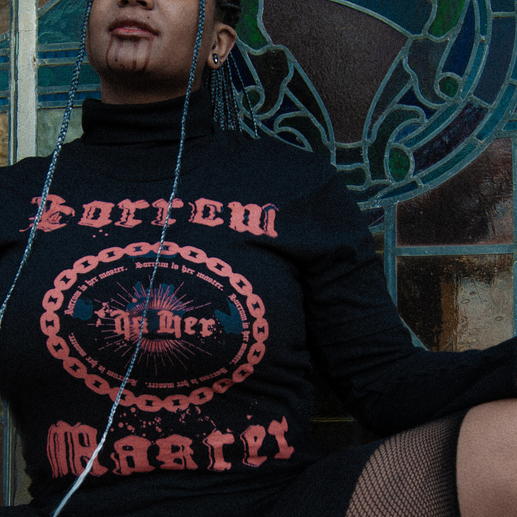 Close up photo of black female alternative model with long grey ombre braids and blood dripping down her lips, wearing a black turtleneck, the Sorrow Is Her Master tee, and short fishnet stockings in front of colored stained glass.