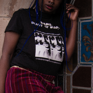 Close up of black goth female model with long black and blue braids and a septum piercing posing in the Darkness Mixed with Light Fitted Tee, a gold chain belt, and dark red velvet pants with gold and blue stripes in front of colored stained glass.