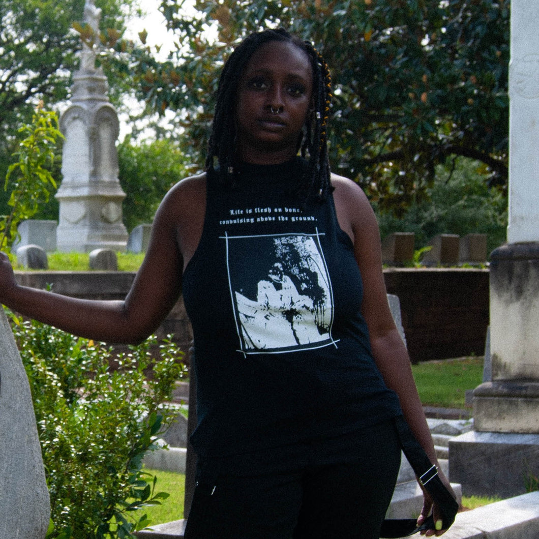 Black woman with braided bob posing in cemetery, wearing A Mysterious Vanishing Sleeveless Mock Neck.