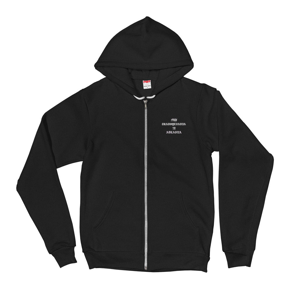 A mockup of a black zip up hoodie with a white drawstring and one embroidered graphic on the upper left chest area that says