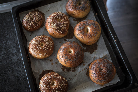 baked sourdough bagels; some topped with sesame seeds and some with poppy seeds