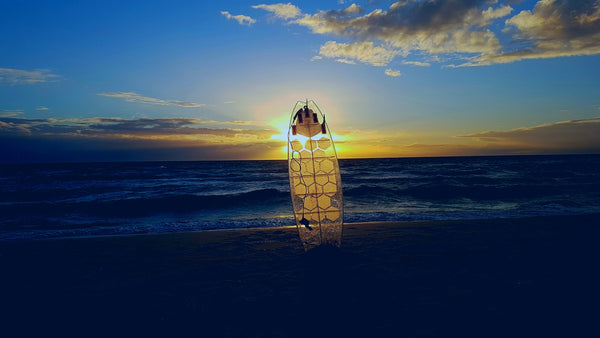 Transparent surfboard with HexaTraction clear traction alternative to wax at sunset