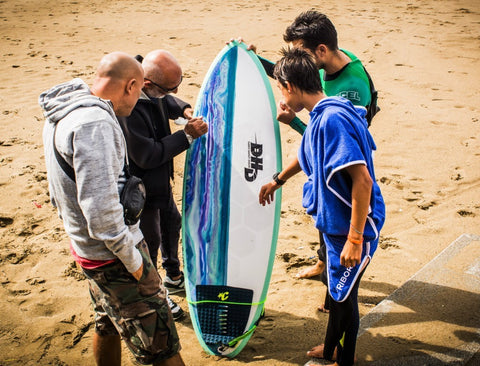 Surfers looking at the HexaTraction on a DHD surf board