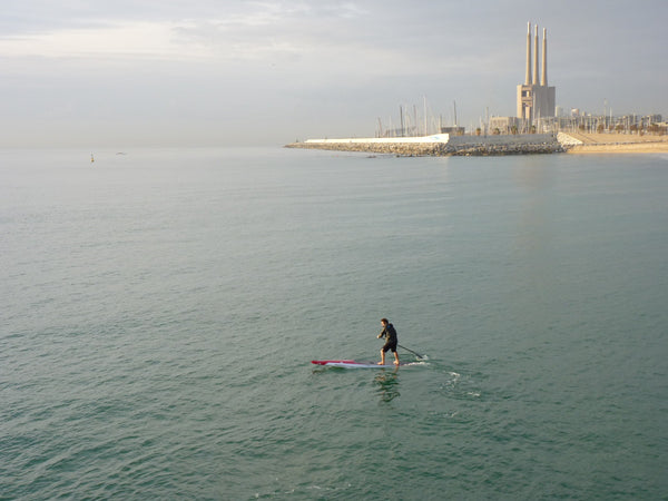 Pepe Oltra RSPro SUP racer paddling between chimneys