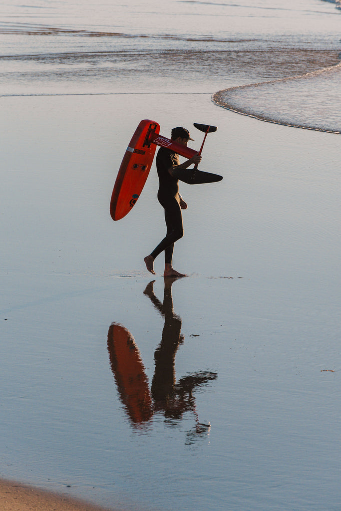 Shannon Stent team RSPro walking down the beach with his foil board