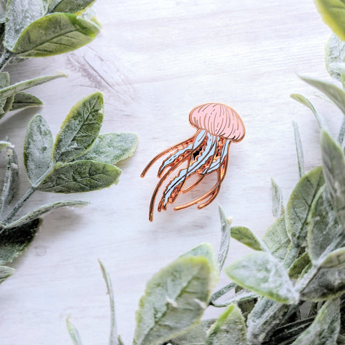 A rose gold pastel coloured enamel pin floating among small green leaves