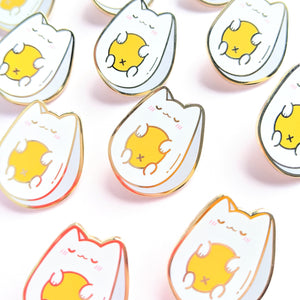 A close up of a group of egg cat enamel pins in bright light