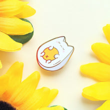Load image into Gallery viewer, A single egg cat enamel pin amidst sunflower petals