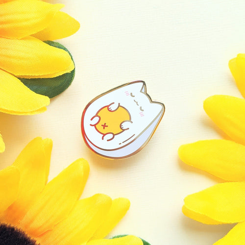 A single egg cat enamel pin amidst sunflower petals