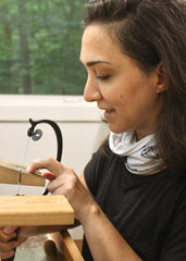 Brooke hand sawing sterling silver at her jeweler's bench.
