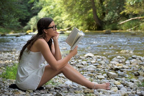 woman sitting reading a book near river