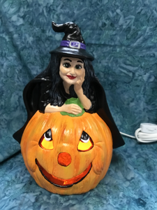 Halloween Witch Leaning On Pumpkin with Light