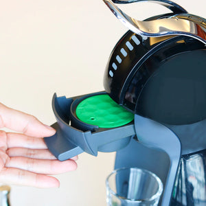 Person putting Reusable Coffee Capsule in Dolce Gusto Machine | Happy Capsules