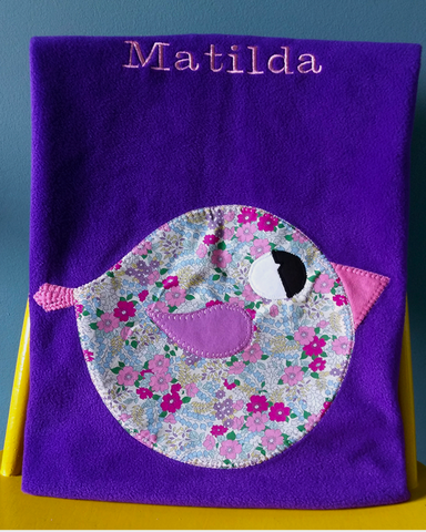 Handmade personalised baby blanket in purple with floral appliqué bird design.