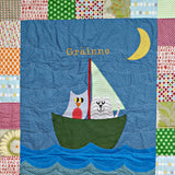Personalised Cotton Quilt featuring the Owl and Pussycat applique in a pea green boat, framed with a patchwork edging.