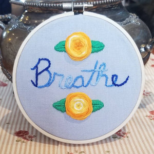 Hand embroidered floral art hoop with the reminder to breathe to reduce anxiety and manage stress