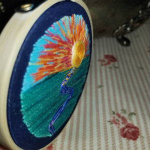 Hand embroidered modern landscape art of a sunrise or set with a river