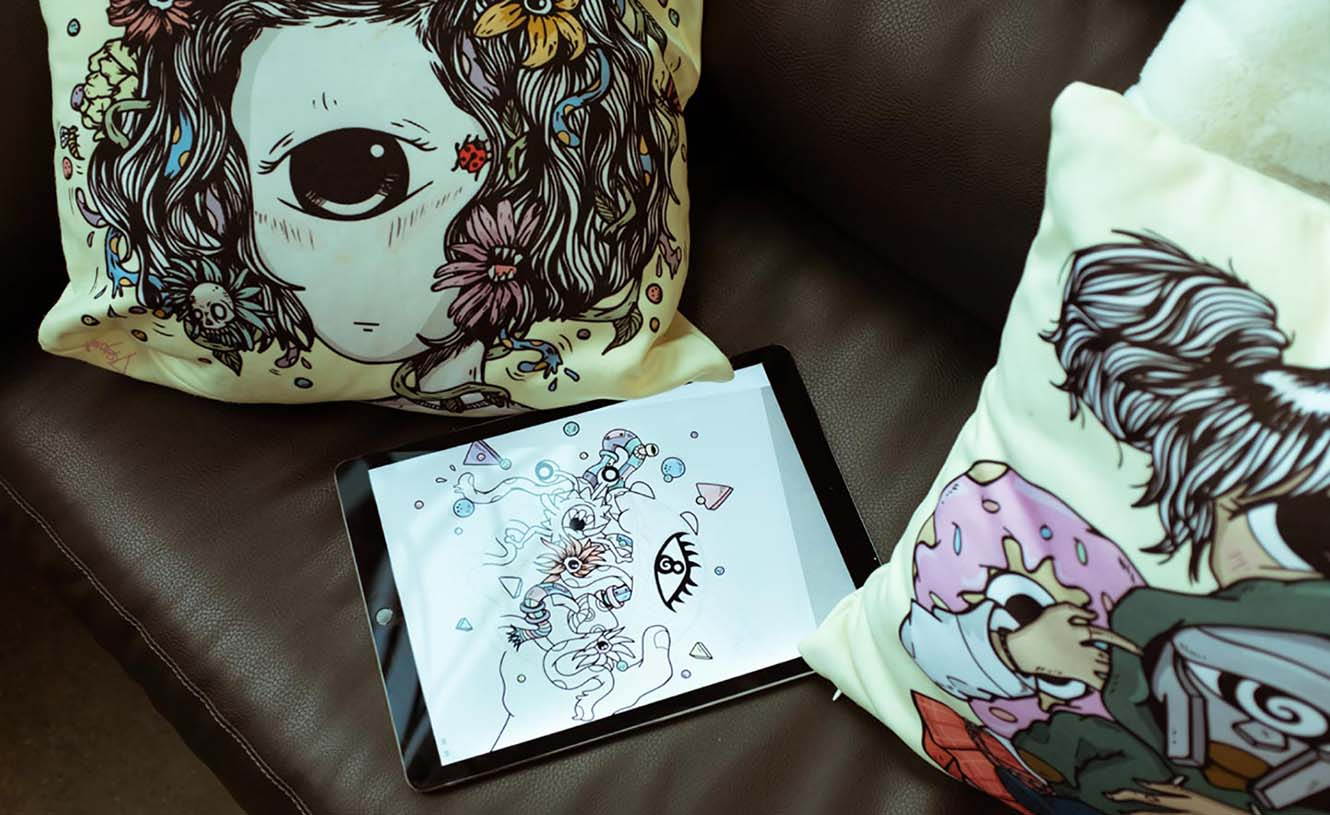 iPad sits on couch displaying Distortedd's magic 8ball illustration, surrounded by 2 pillows featuring Distortedd's signature eyeball illustrations