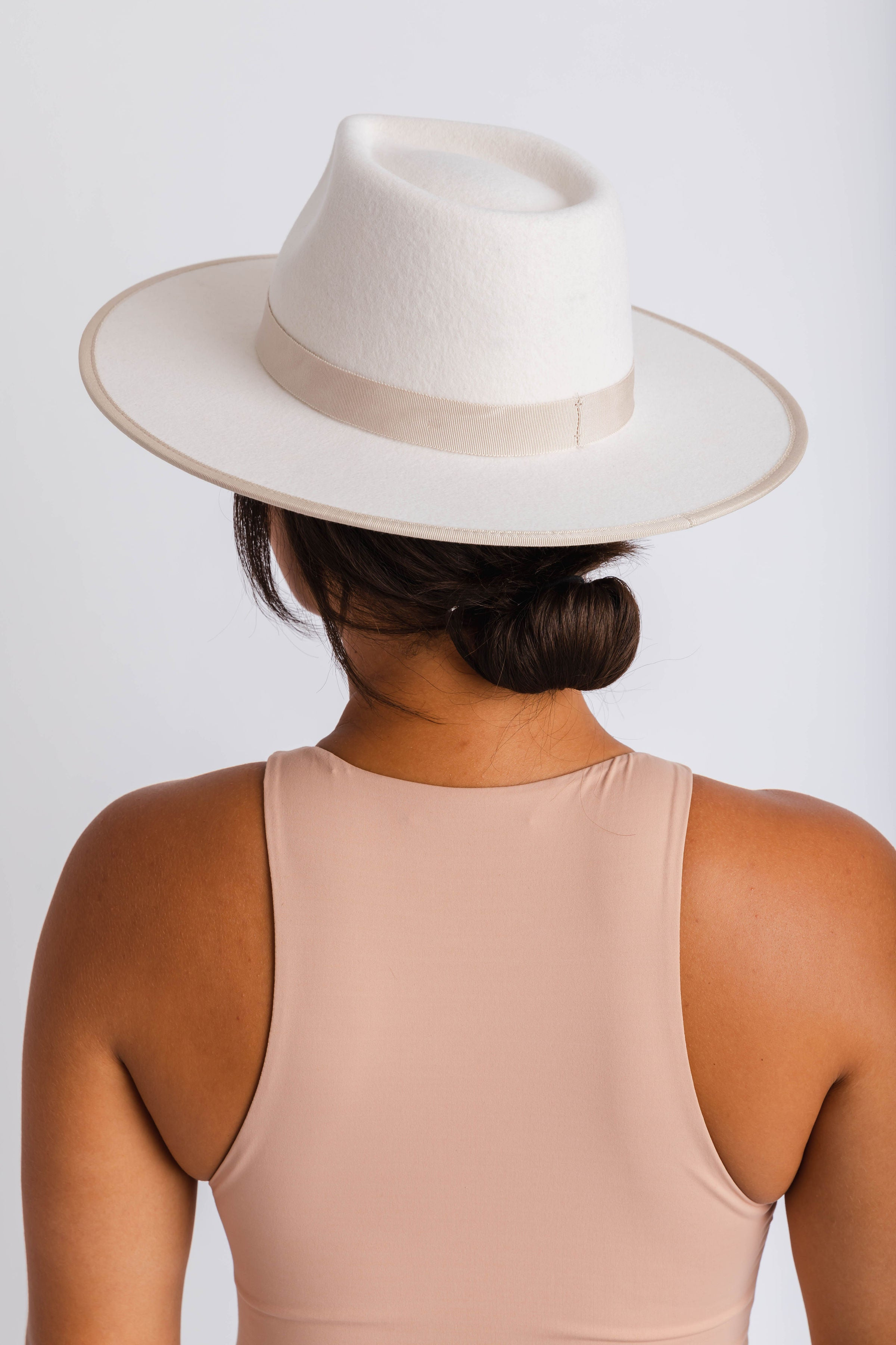 The Rae is a women's stiff ivory fedora with a light beige grosgain ribbon trimmed on the crown and the brim.